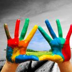 Painted colorful hands showing way to colorful happy life, conceptual.