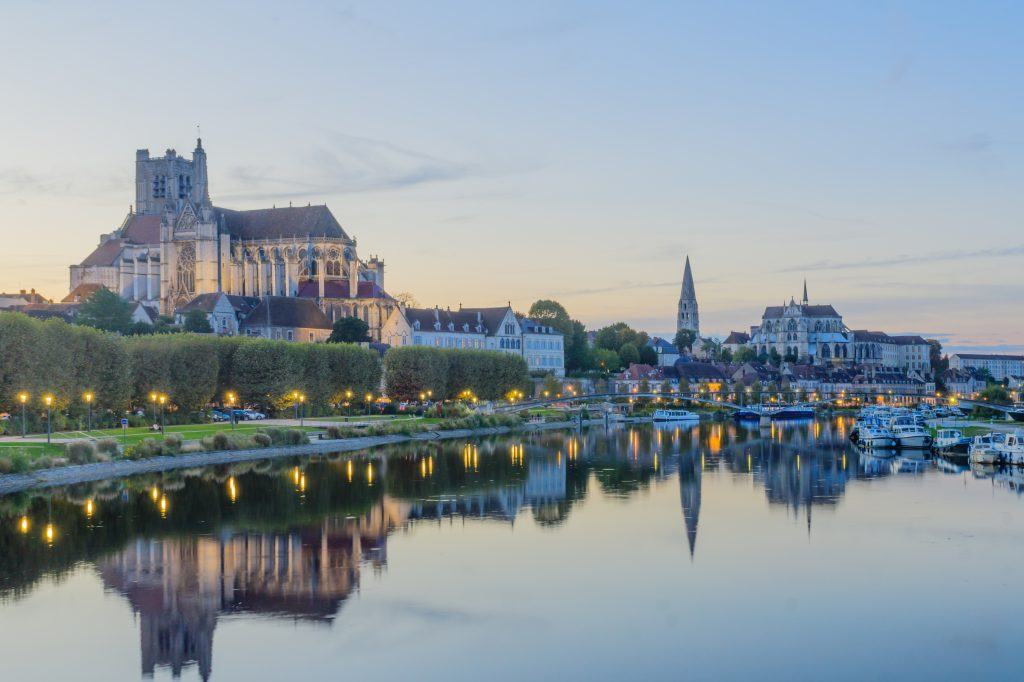 Sunset view of the Yonne River, with boats, the cathedral (Cathedrale Saint-Etienne), the Abbey of Saint-Germain, locals and visitors, in Auxerre, Burgundy, France